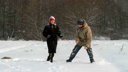 sporty zimowe : The young man and the girl throw each other snow