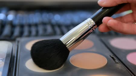 kartáč : Close up view of makeup brush moving over skin and eyeshadow color palette Dostupné videozáznamy