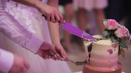 wed : Close up of a bride and groom cutting their wedding cake.