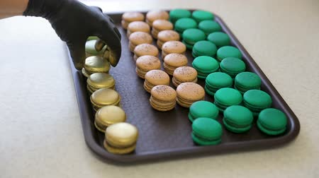 dark green : Multicolored macaroons freshly prepared and ready for sale. Chef puts a prepared macaroon on plate