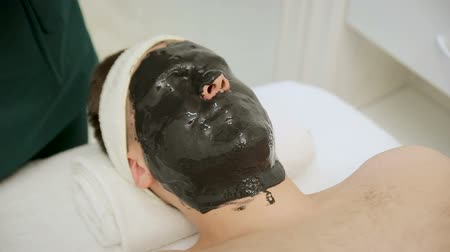 akne : Spa therapy for handsome men receiving facial mask. Reception of a cosmetologist