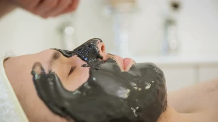 dermatologia : The beautician puts a black mask on the man, applying a rejuvenating cosmetic mask of black tissue to the face Stock Footage