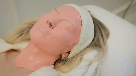eye mask : Beautiful woman with pink facial mask at beauty salon. Spa treatment. Stock Footage