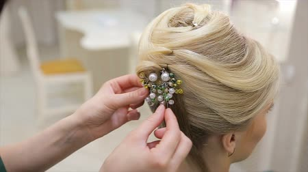 Hairdresser attaches a decoration to the hair of a young blond haired woman, close-up