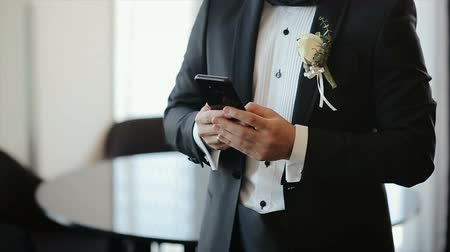 toegangscontrole : Man in Suit Using his Phone for Social Network. Groom Texting Massage to the Bride. Blogging.Smartphone