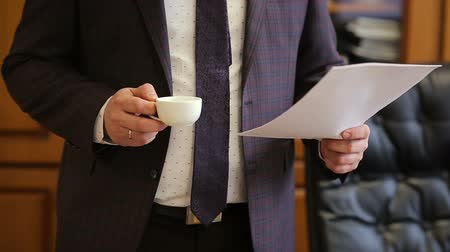 cup : Businessman reading documents and drinks coffee from coffee cup while working late in the office