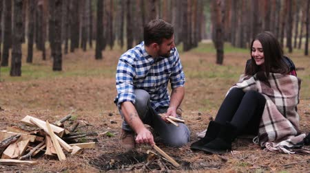 şenlik ateşi : Young couple in the forest. A man is building a fire