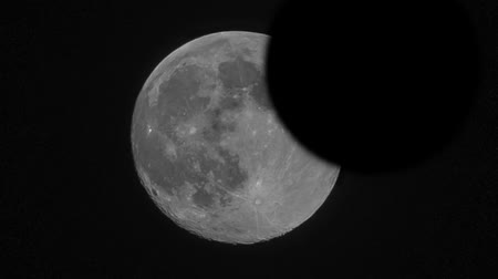 Video of a lunar eclipse over a big moon almost covered by the earth shadow Stock mozgókép