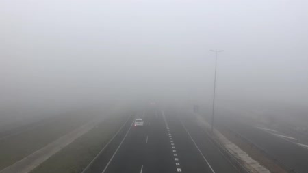 self driving : Cars And Trucks Vehicle Traffic On A Highway On A Dense Fog Day Stock Footage