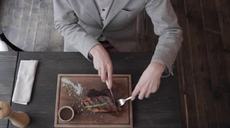 bıçak : A young man eating a juicy steak with sauce and spices in a restaurant with a knife and fork on a cutting board