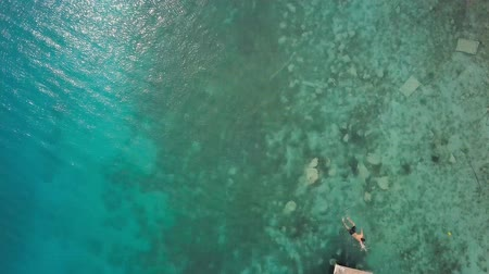wanderlust : BACALAR, MEXICO, 06 OCTOBER 2017: young man swimming to wooden pier - shot from drone