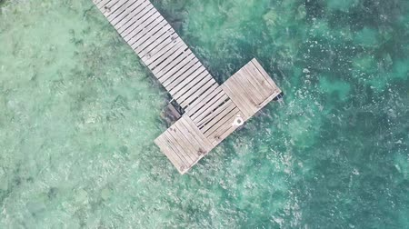 tyrkysový : Wooden pier and blue waters around - screwdriver view shot from drone Dostupné videozáznamy