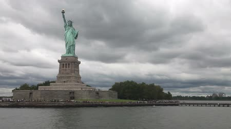 статуя : Statue of Liberty in a cloudy day with long line of people waiting to visit