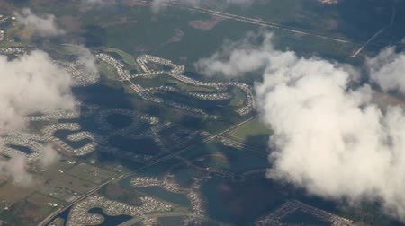 voar : Flying above clouds and land, Aerial view from an airplane over Florida, US Stock Footage