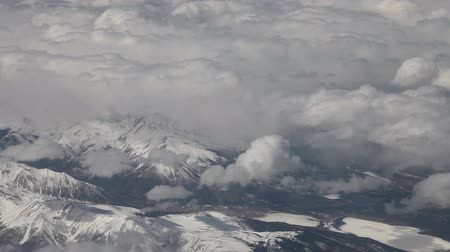 bílé mraky : Aerial view from an airplane over the west coast of the US, mountains covered with snow, and frozen lakes, lots of clouds, realtime. Dostupné videozáznamy