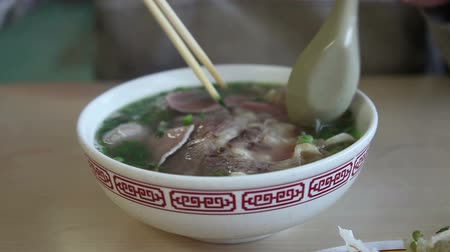 Traditional Vietnamese Pho Bo (beef noodle soup) with someone eating it.