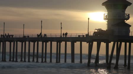 západ : Sunset at the pier , Huntington Beach, California, people walking around, some are still surfing and swimming.
