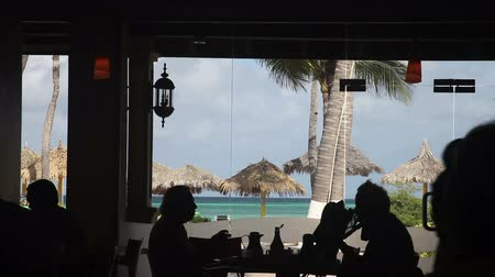People enjoy morning breakfast in a dining room of a beach resort, Palm beach, Aruba, the Caribbean.
