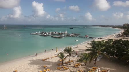Palm beach with pier , Aruba, the Caribbean, quiet in the morning with people walking, jogging, view from above.