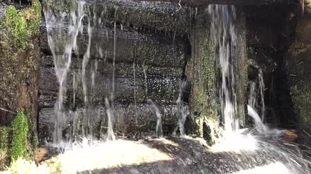 típico : Close-up of water flowing from the slit of a weathered wooden canal lock gate. Strong high pressure water splashing and making white bubbles.