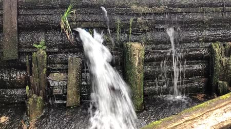 yarık : Close-up of water flowing from the slit of a weathered wooden canal lock gate. Strong high pressure water splashing and making white bubbles.