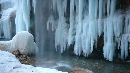 icefall : beautiful view of frozen waterfall with turquoise river, global warming concept