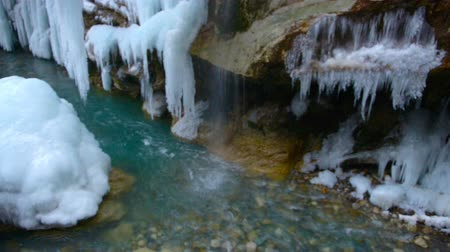 icefall : beautiful scene of frozen waterfall with blue icicles and turquoise river, spring concept