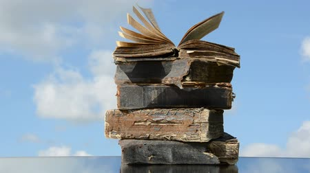 religioso : old books on mirror on sky background and wind