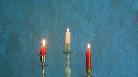świecznik : three candlesticks with candles on blue background  Wideo