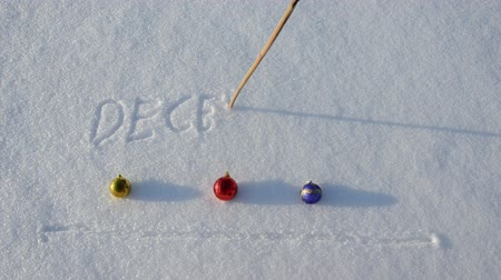 neve : writing word December on snow and Christmas balls