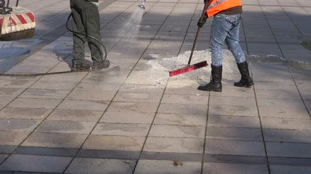 anyagi : workers cleaning city square granite pavement