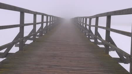 wooden path : dark and mystical early morning fog on old empty wooden bridge