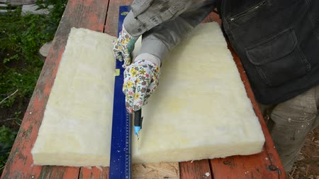 yalıtım : worker with knife cutting rockwool for house insulation