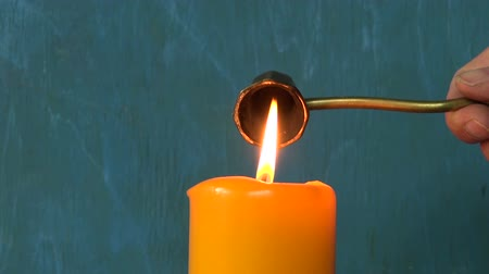 extinguishing : extinguishing yellow candle flame with brass bell tool Stock Footage