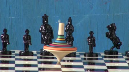 xadrez : black chess and colorful  wooden toy whirligig on chessboard