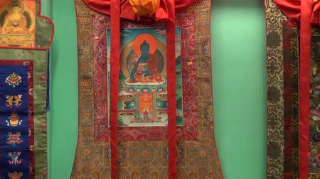 iconography : DHARAMSALA, INDIA – DEC 18, 2012: Tibetan artist  traditional Thangka  painting and other souvenirs in shop Stock Footage