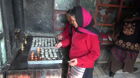 sürgün : NEPAL, KATMANDU – DECEMBER 19, 2013: Tibetan buddhist woman prayers in Katmandu Swayambhunath stupa. Buddhist prayer wheel and candles - Katmandu, Nepal, December 19, 2013