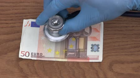 problem : economist with stethoscope looking euro banknote health condition