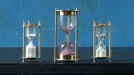 três : sand motion in three sandglass, sand clock. Time concept