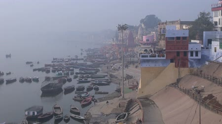 morning : VARANASI, INDIA, DECEMBER 2012: cold early morning fog and smog in sacred Ganges river with boats Stock Footage