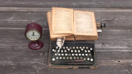 tipo : ancient typewriter and old book on wooden background. Wind in book page Vídeos