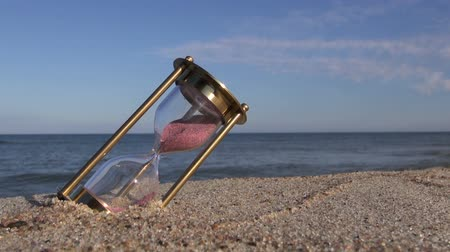sandálias : brass ancient hourglass sandglass clock on sea beach sand. Summer time concept