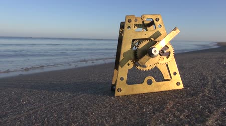 time machine : antique brass clock gears on autumn sea beach sand. Time and ocean concept