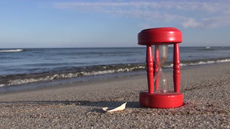 sandálias : ancient red broken hourglass sandglass clock on sea beach sand. Summer time concept