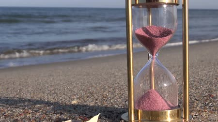 sandálias : red sand motion in ancient brass sandglass hourglass on sea beach sand Stock Footage