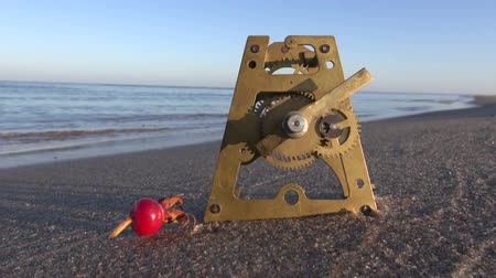 kum saati : antique brass clock gears and rose hip on  sea beach sand. Time and ocean concept