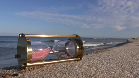 sandálias : ancient brass sandglass hourglass on sea beach sand Stock Footage