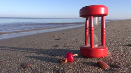 sandálias : ancient red broken hourglass sandglass clock and rose hips on sea beach sand. Summer time concept