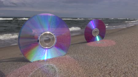 compact disc : Two CDs on sea beach sand and waves