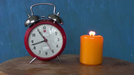gyertyák : Retro alarm clock with a burning candle with blue background